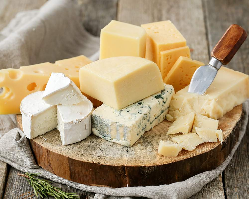 different types of cheese that has tyrosine on a wooden cutting board