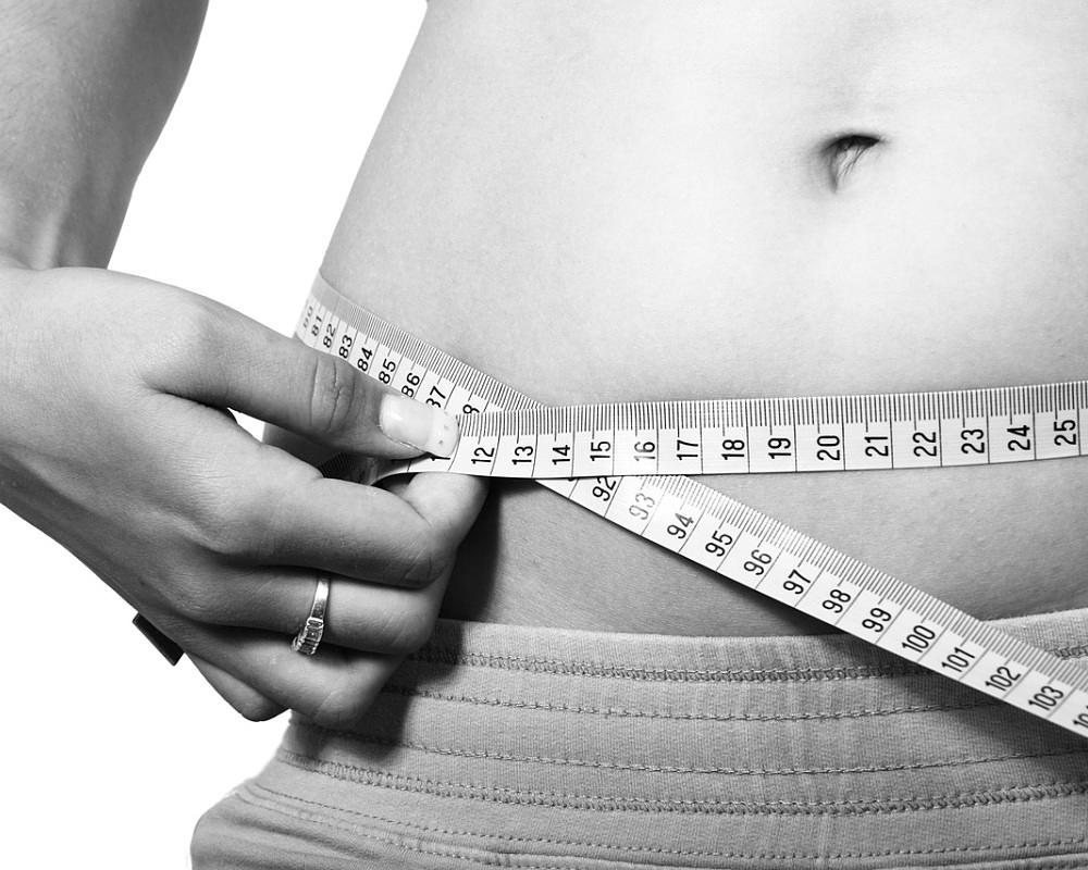 Woman measuring waste to track weight loss