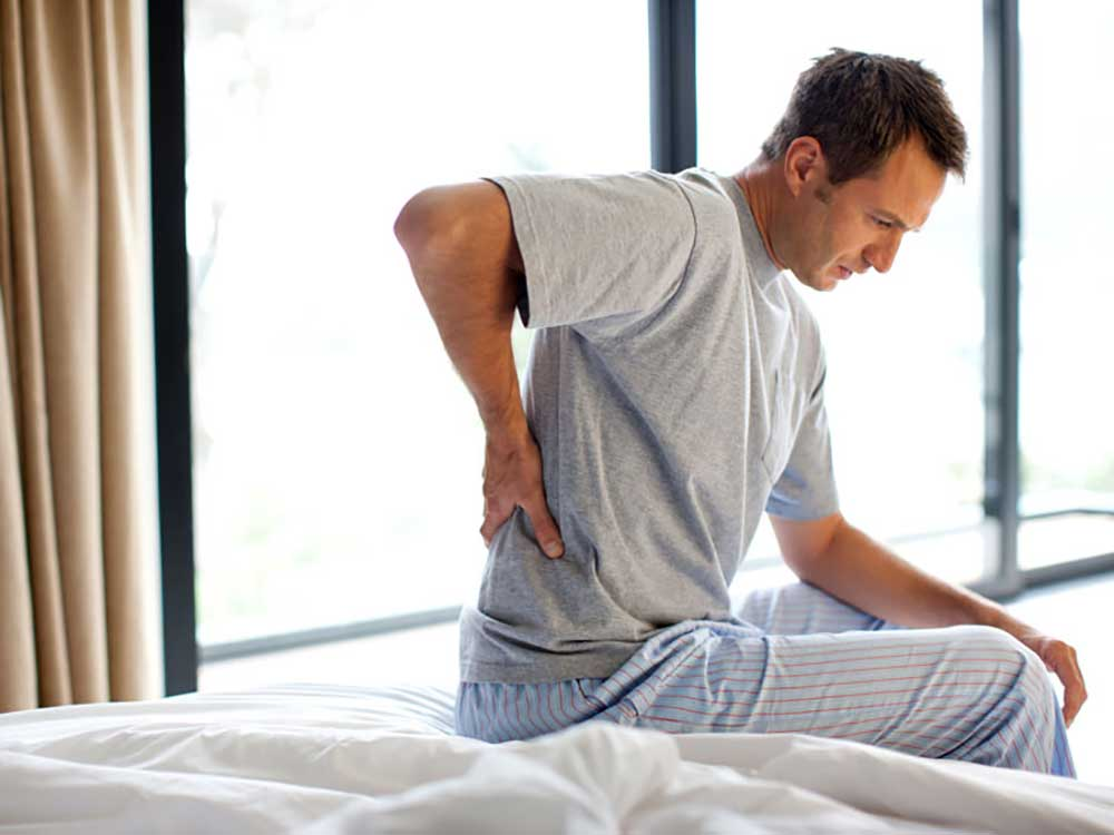 man in pajamas having back pain