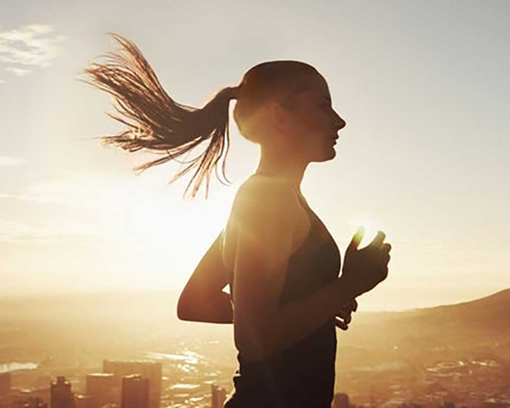 woman running with sunrise background