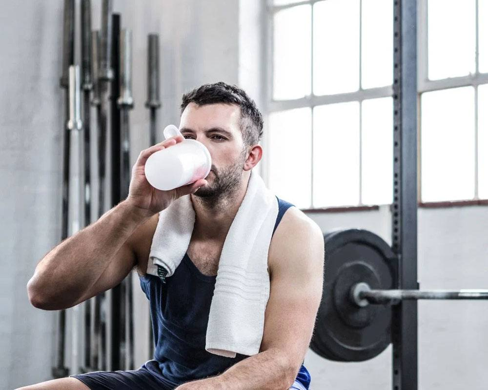 muscled man sitting inside the gym drinking protein shake