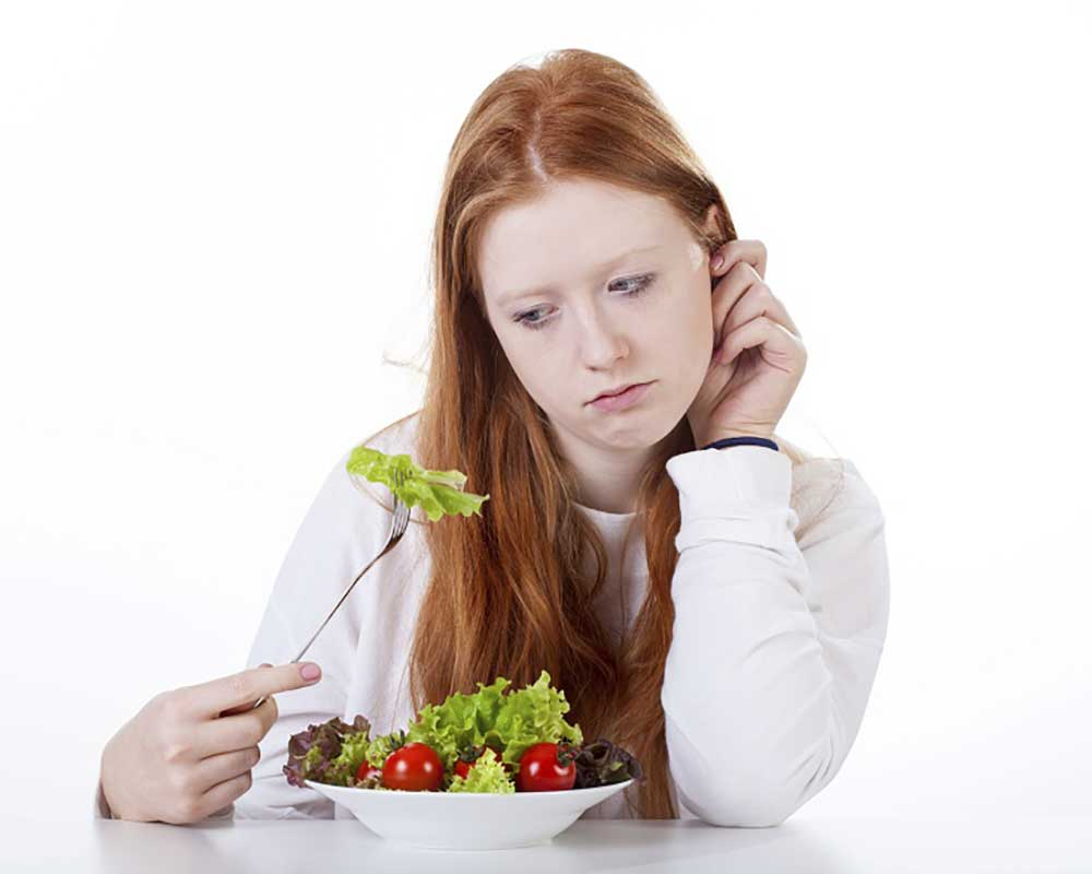 woman sad while eating a bowl of vegetable salad