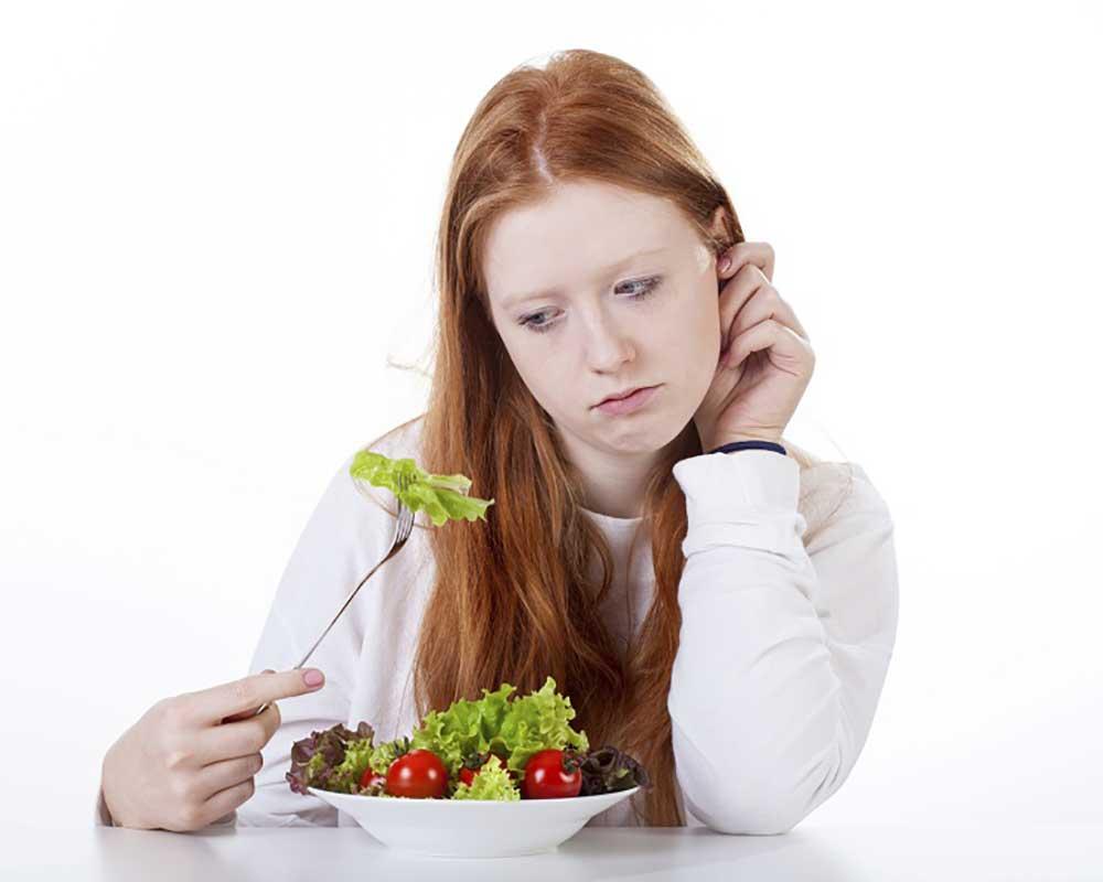 woman sad while eating a bowl of vegetable salad
