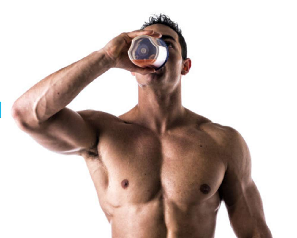 Muscled man drinking protein drink